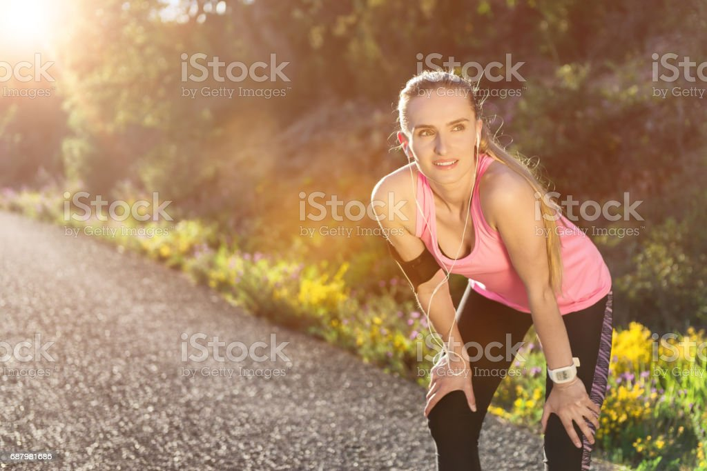 Young runner relaxing & smiling during exercise stock photo