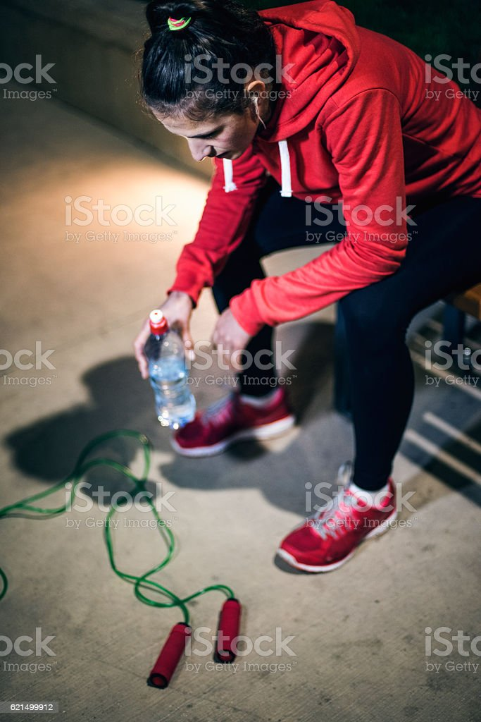 Young runner resting on bench stock photo