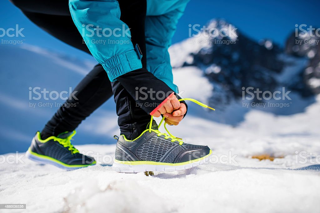 Young runner tying her shoelaces stock photo