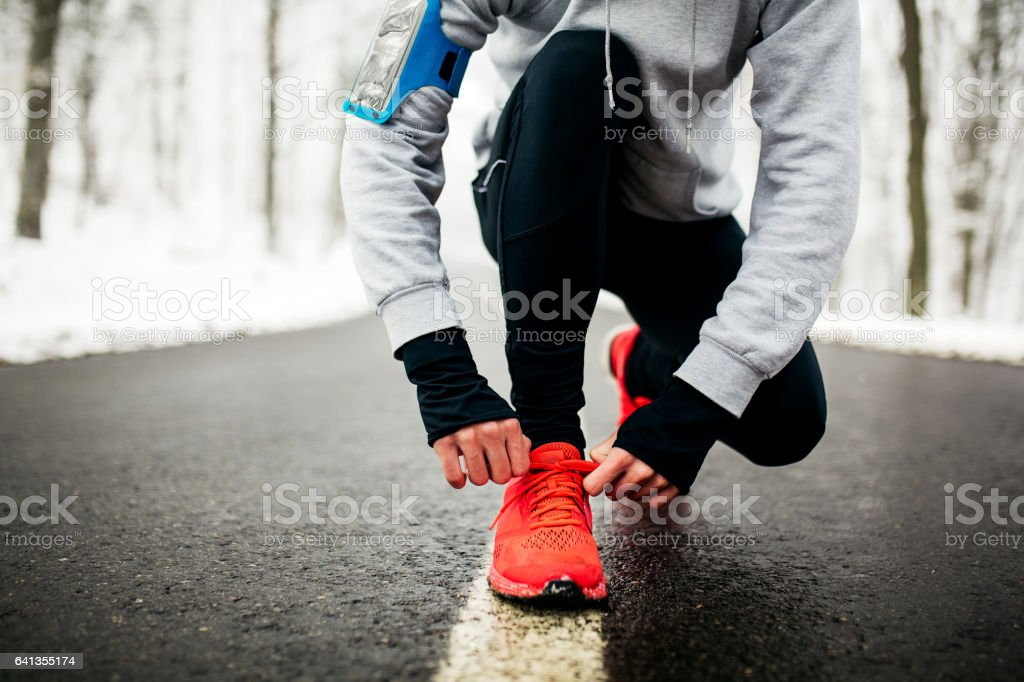 Young runner tying his shoelaces stock photo