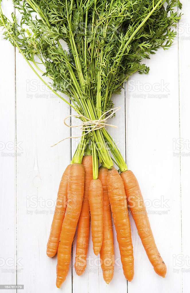 Young rustic carrots on white boards royalty-free stock photo