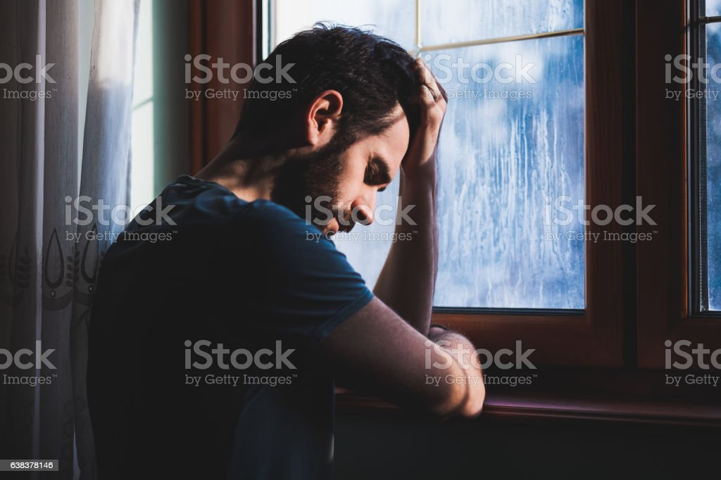 Young sad mad sitting in regret stock photo
