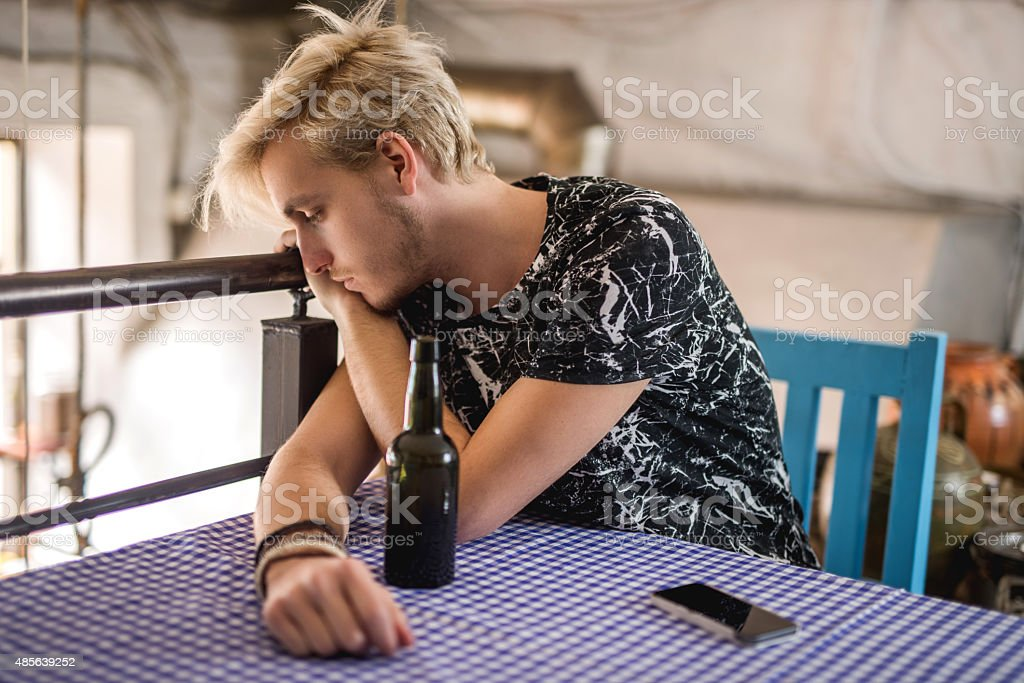 Young sad man had too much beer in a cafe. stock photo