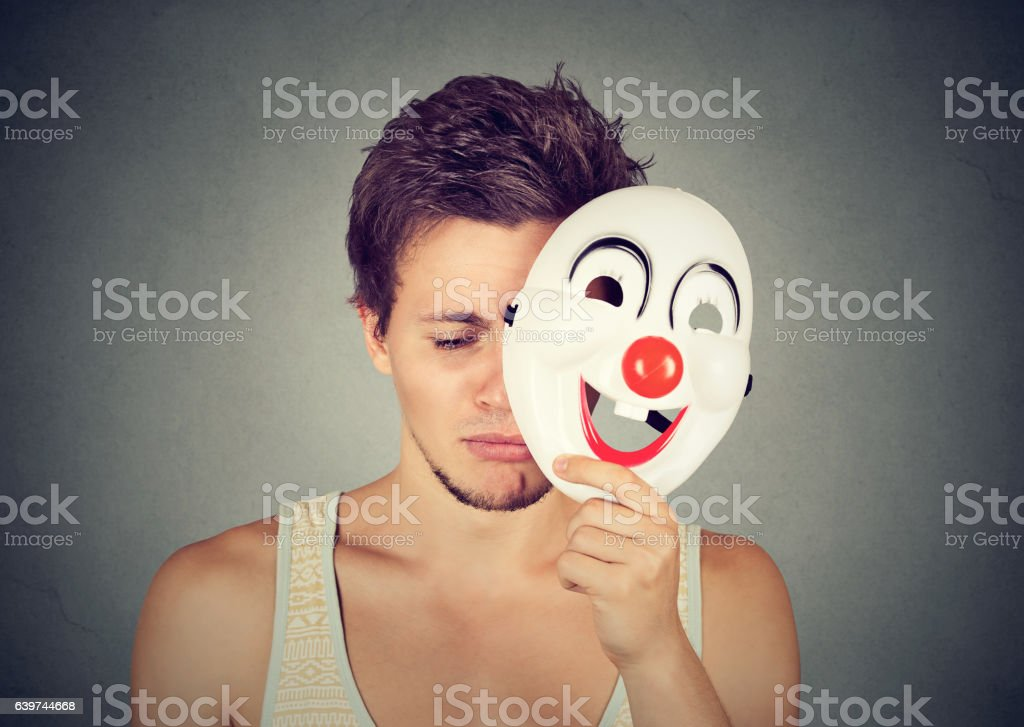 Young sad man taking off clown mask stock photo