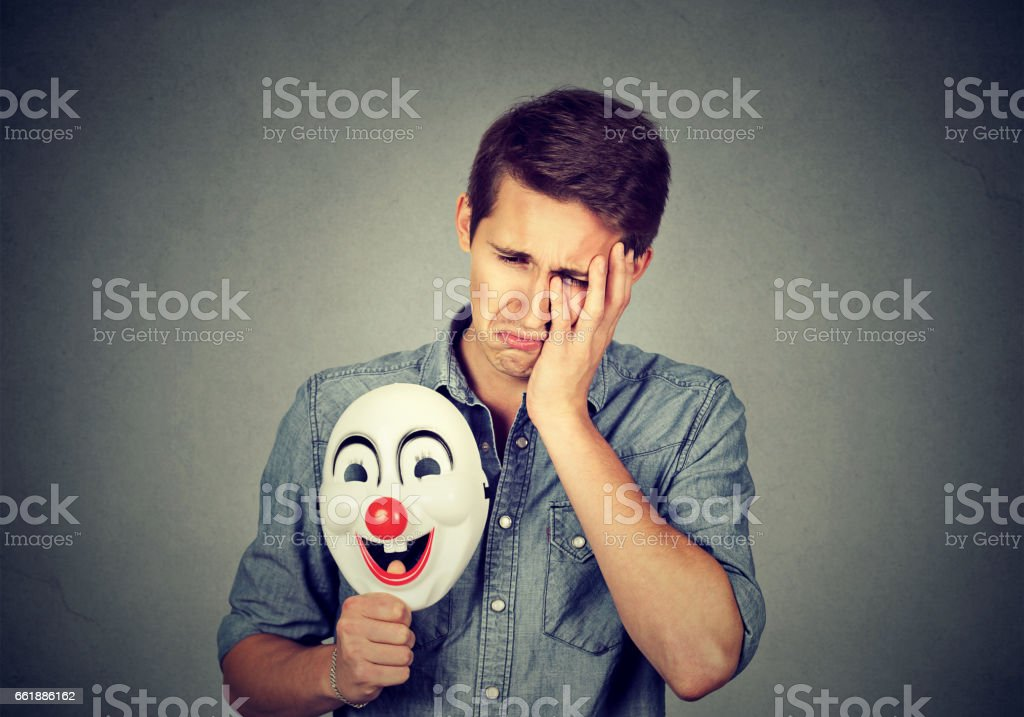 Young sad man with happy clown mask stock photo