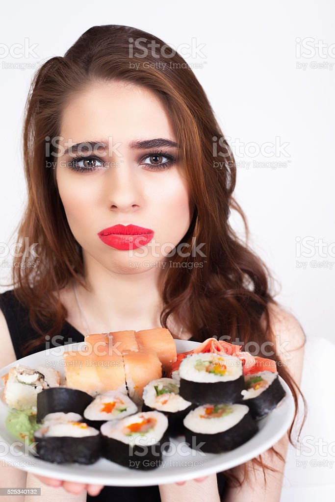 Young sad woman holding a plate of sushi stock photo
