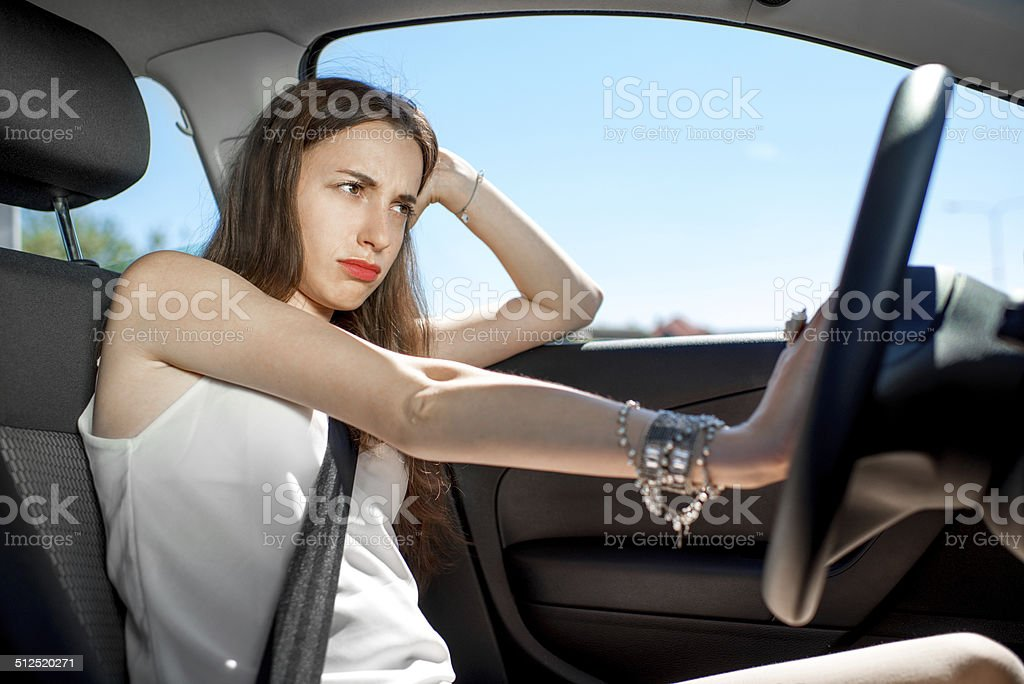 Young sad woman hurry to work while standing in traffic stock photo