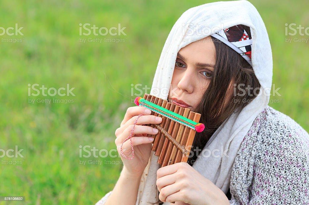 Young sad woman playing panpipe stock photo