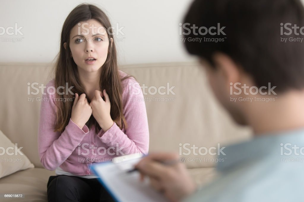 Young sad woman telling about her problem to male psychotherapist stock photo