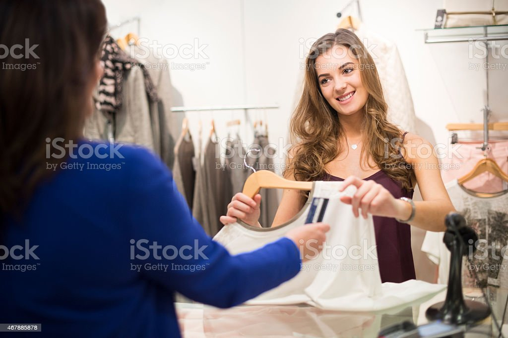 young sales assistnat smiling to customer stock photo