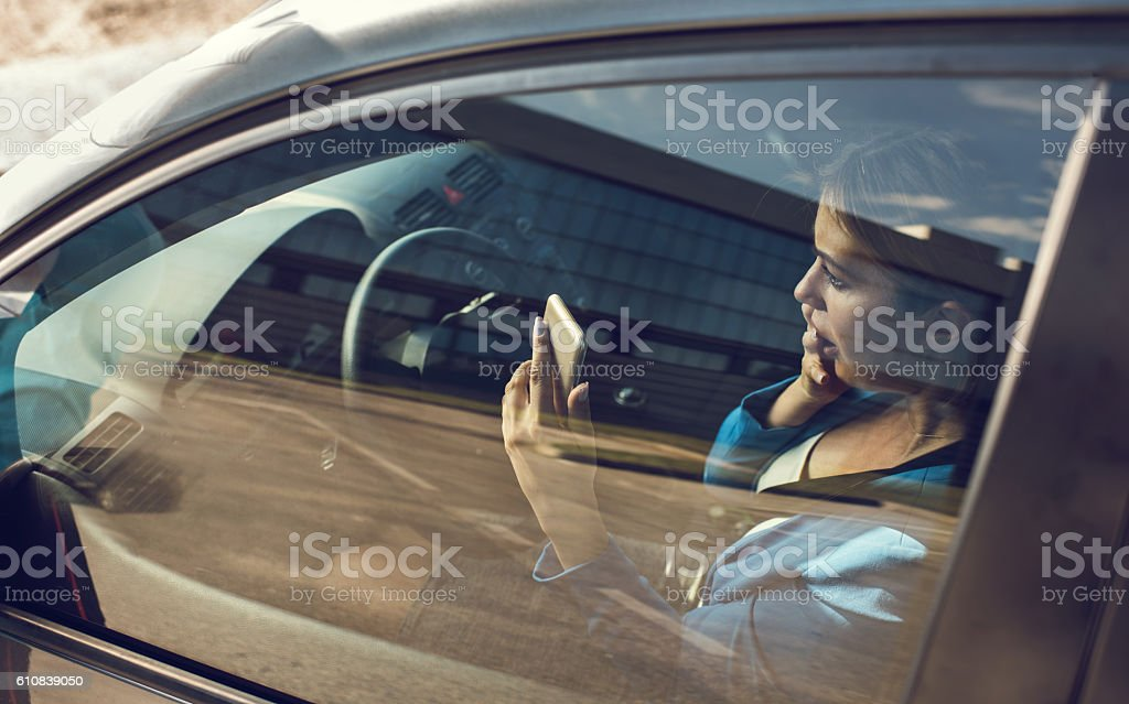 Young scared businesswoman using cell phone while driving a car. stock photo