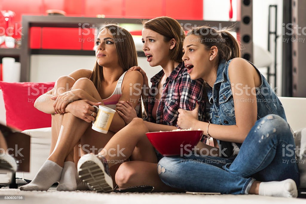 Young scared women watching horror movie at home. stock photo