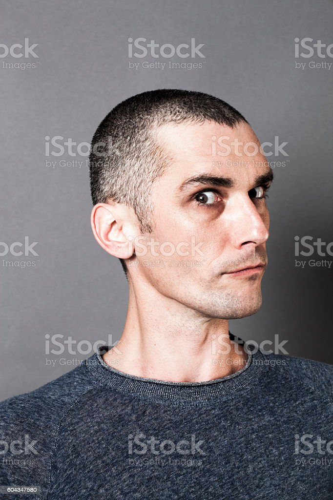 young scary man acting superior, expressing suspicion and unhappiness stock photo