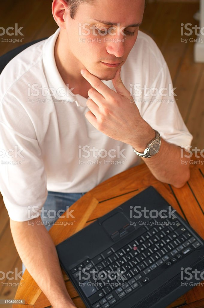 Young sceptical businessman looking at laptop royalty-free stock photo