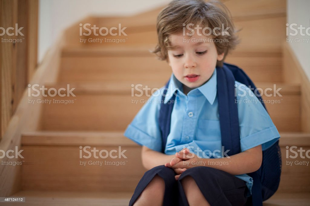 Young school boy sitting sad on stairs in uniform stock photo