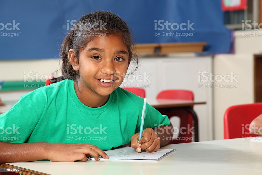 Young school girl 9 writing at her classroom desk stock photo