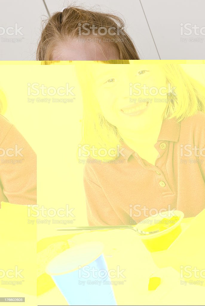 Young school girl smiling while eating lunch royalty-free stock photo