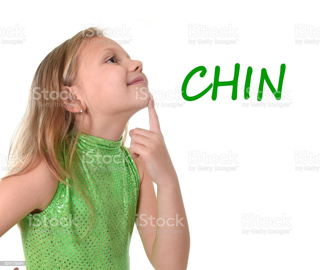 young schoolgirl pointing chin in body parts learning English words stock photo