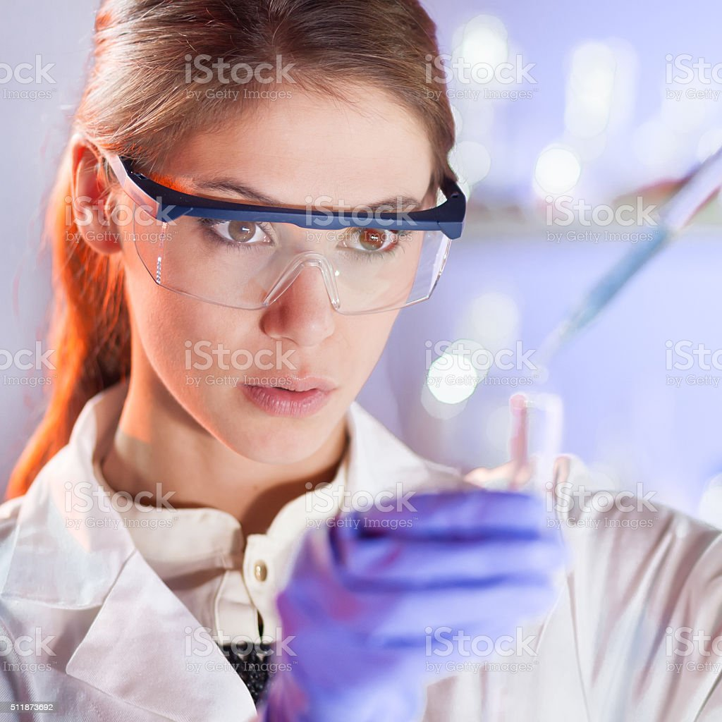 Young scientist pipetting in life science laboratory. stock photo