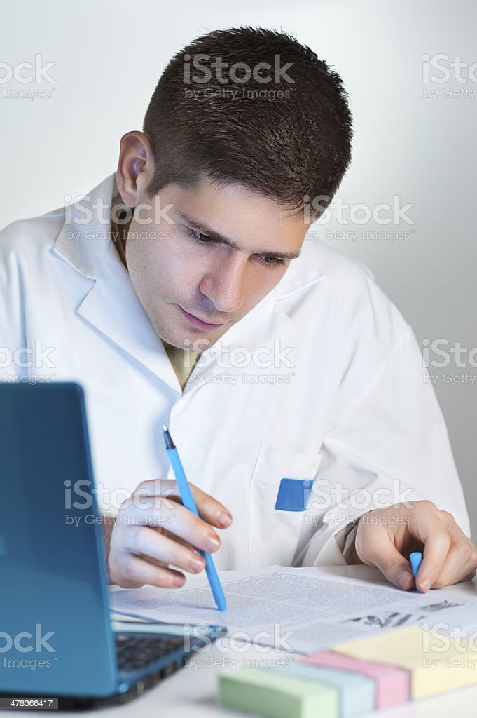 Young scientist reads fresh publication stock photo