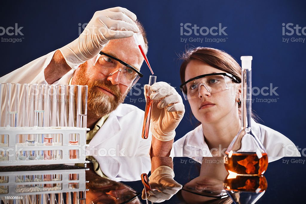 Young scientist watches mentor demonstrating technique in lab royalty-free stock photo