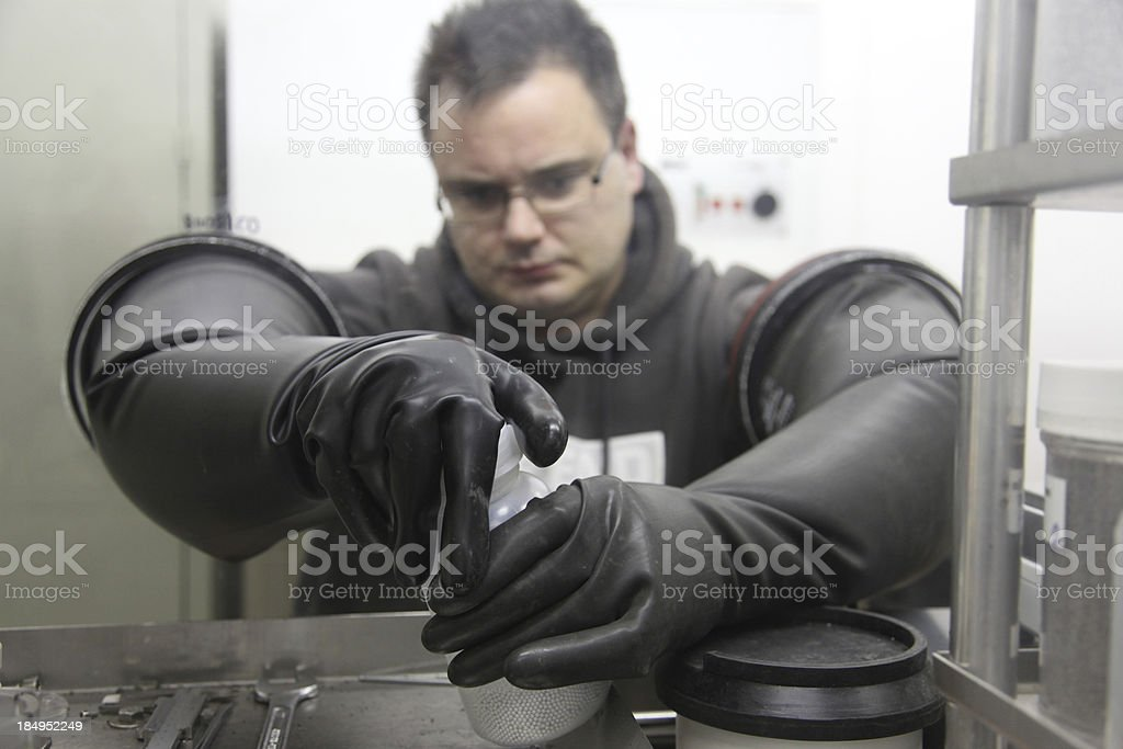 Young scientist working in a glove box stock photo