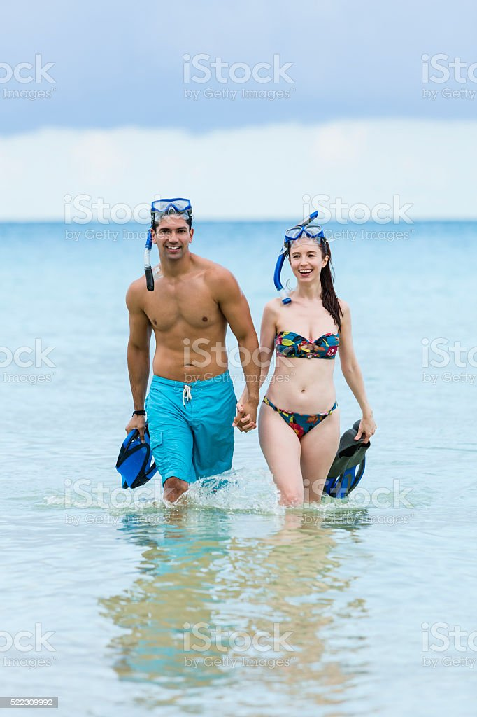 Young scuba couple holding hands and walking in ocean stock photo