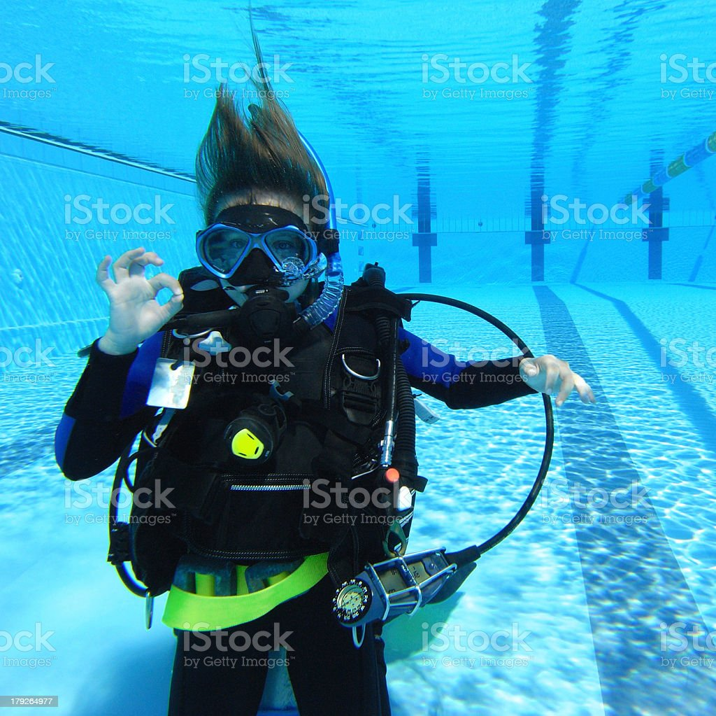 Young scuba diver in a swimming pool signaling OK stock photo