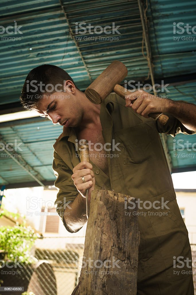 Young Sculptor Artist Working And Sculpting Wood Statue-5 stock photo