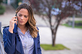 Young serious businesswoman using phone on the street
