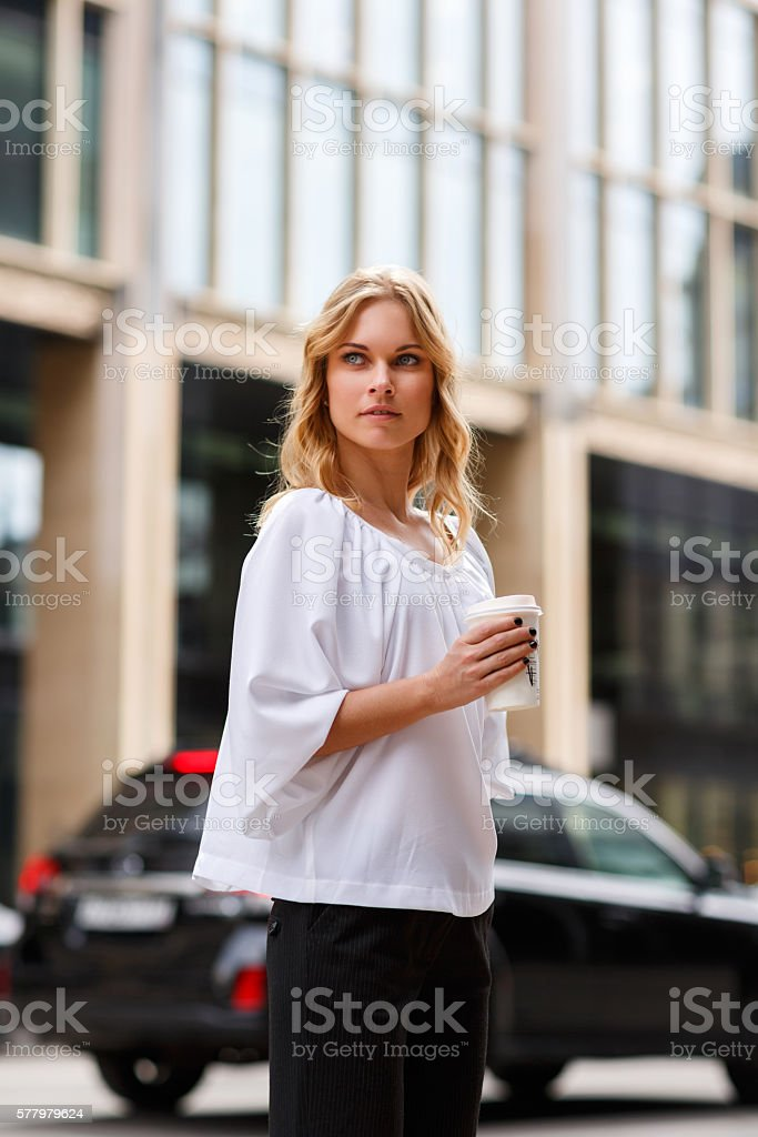 Young serious businesswoman with coffee to go on building background stock photo