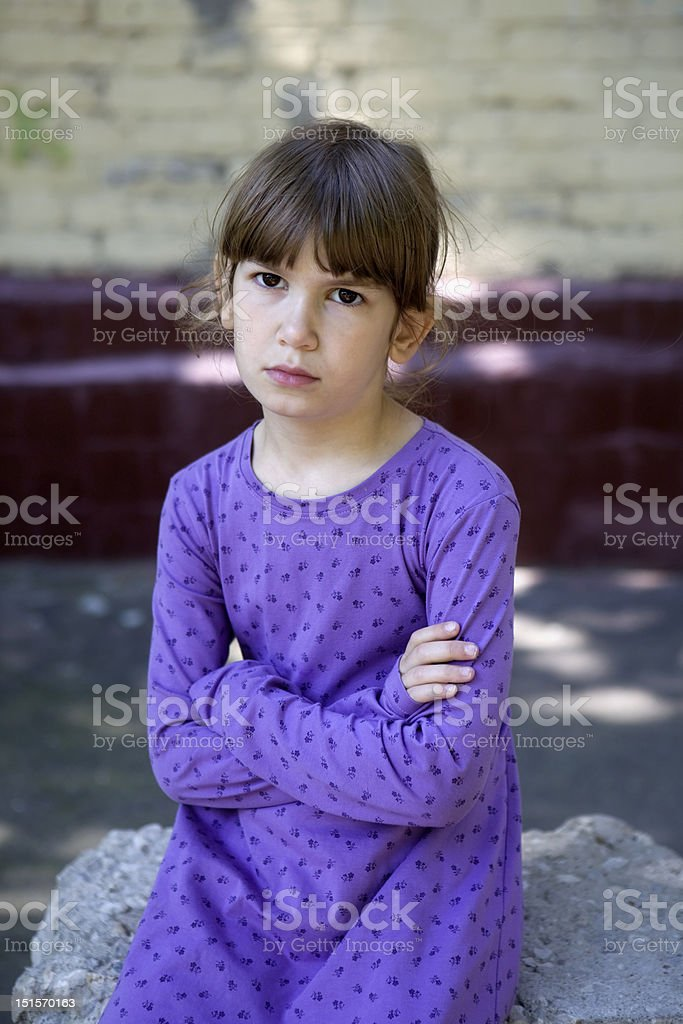 young serious girl sitting on stone royalty-free stock photo