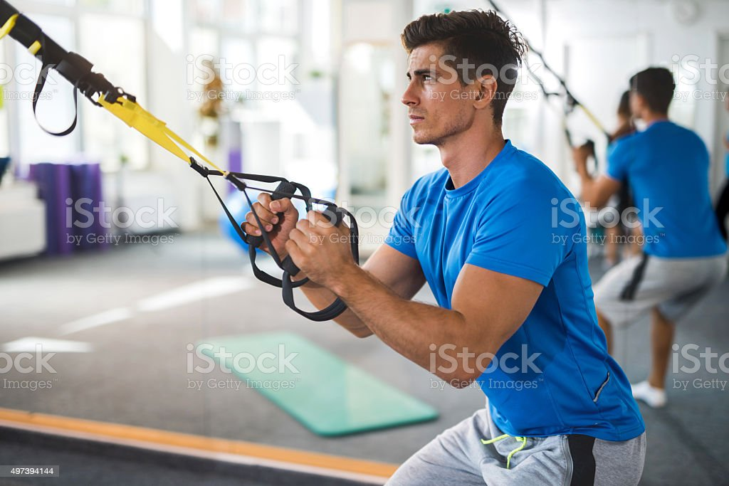 Young serious man exercising on Pilates class in health club. stock photo