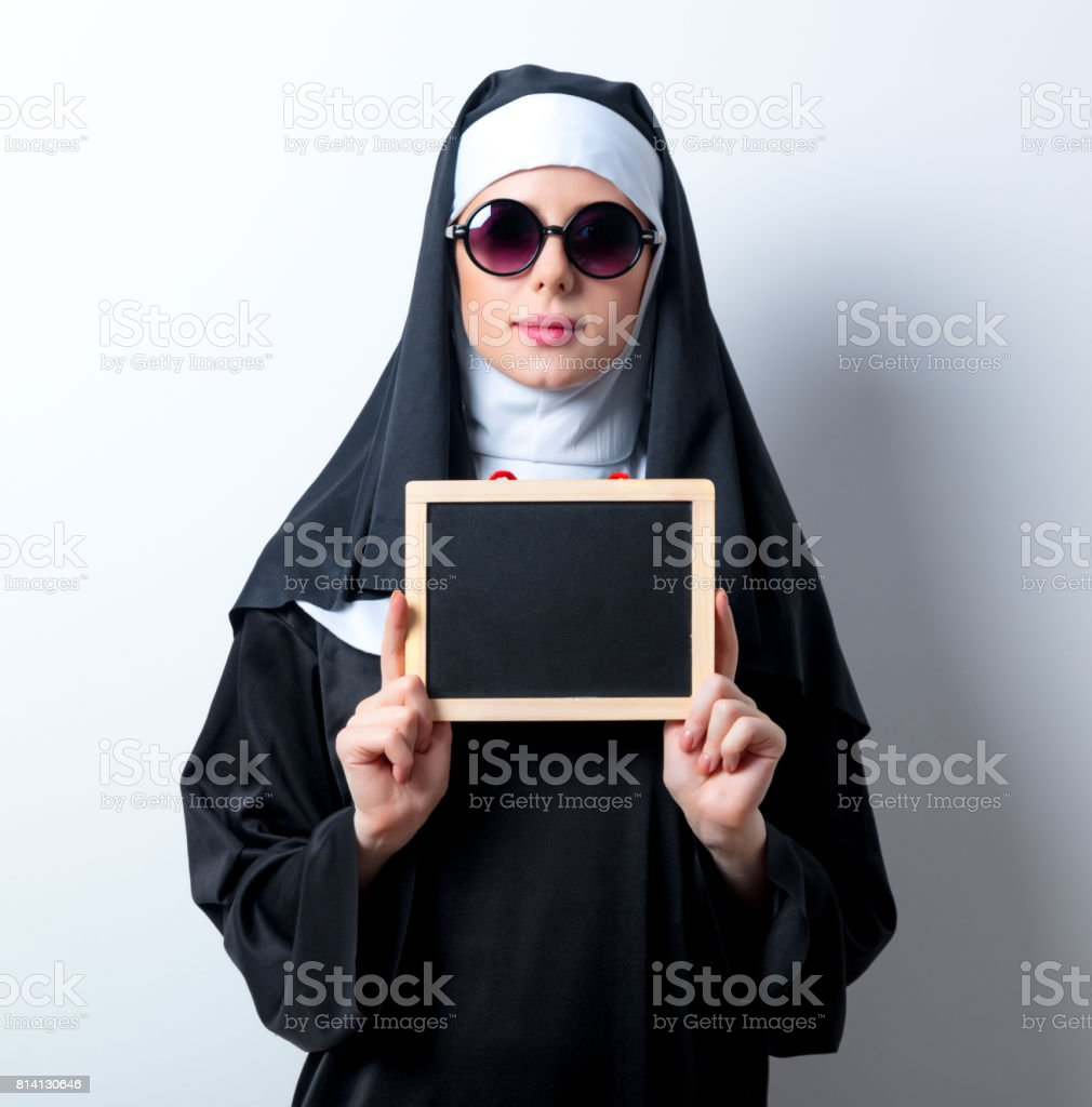Young serious nun with board stock photo