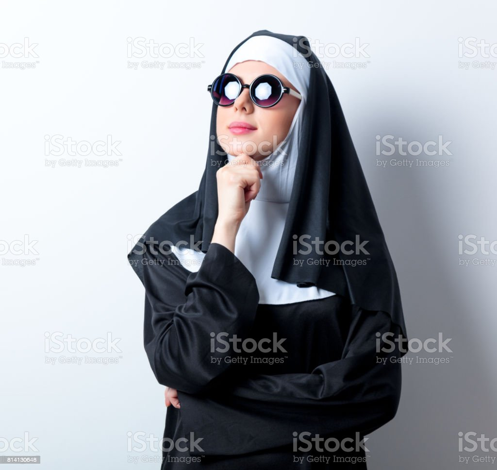 Young serious nun with sunglasses stock photo