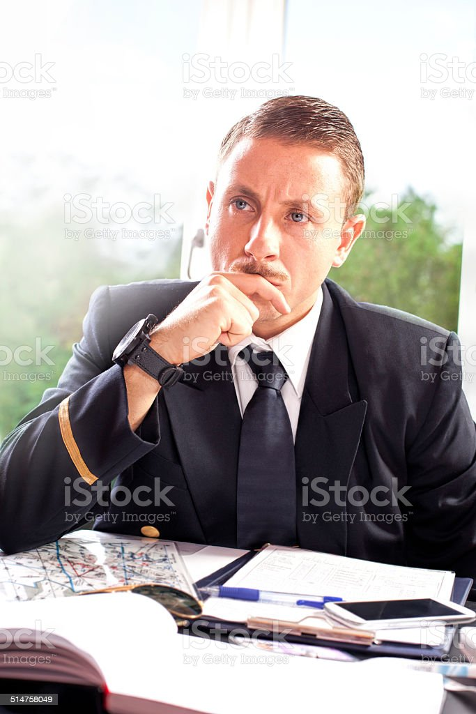 Young serious pilot in the office stock photo