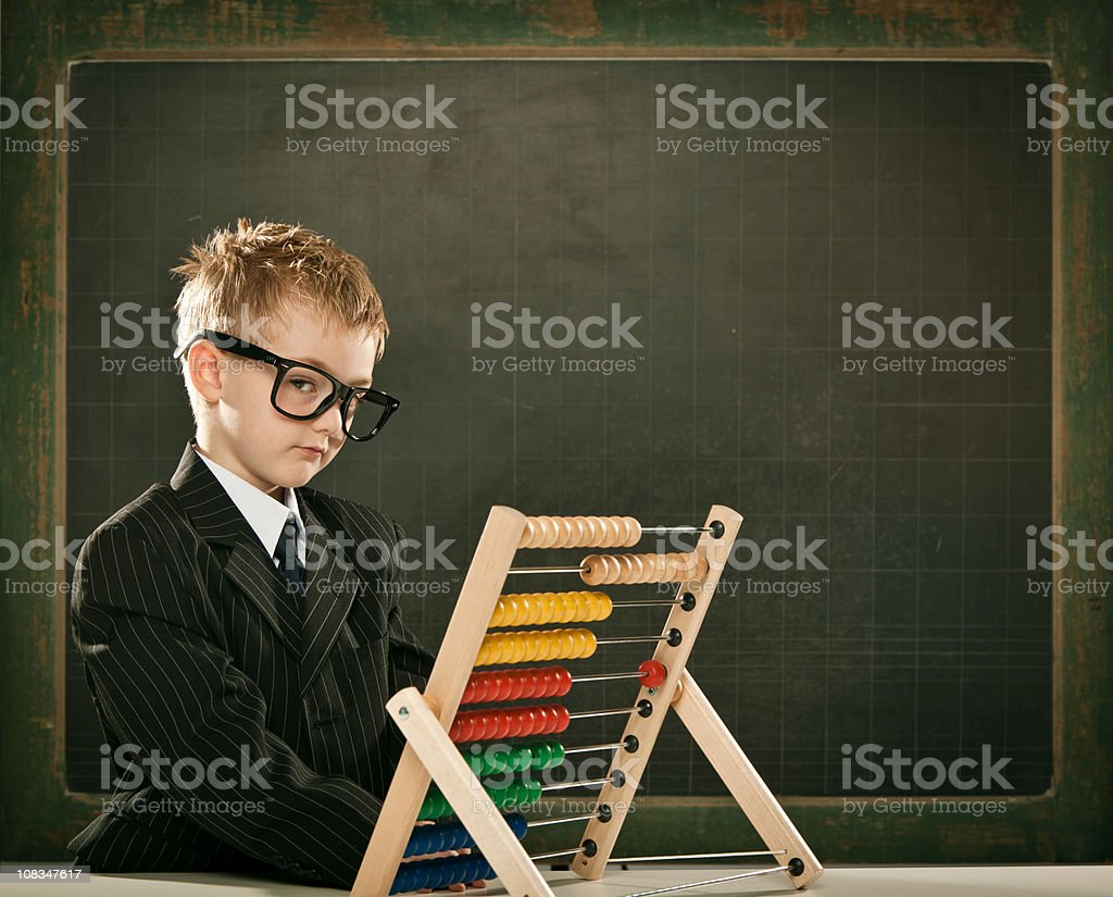 young serious scientist child with abacus and copyspace blackboa royalty-free stock photo