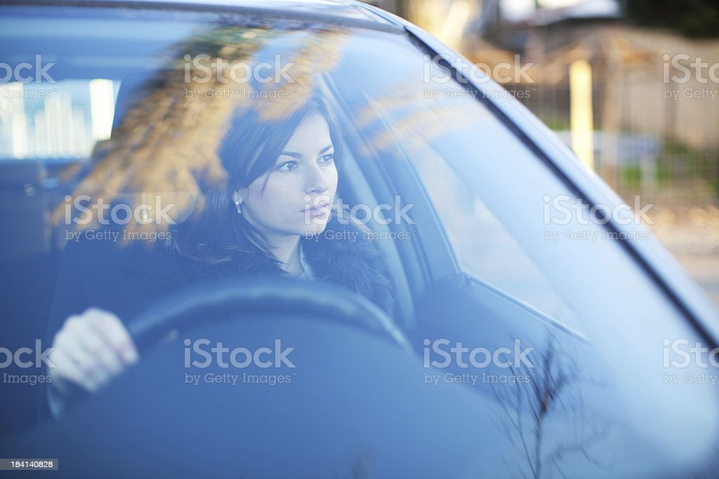 Young serious woman is driving a car stock photo