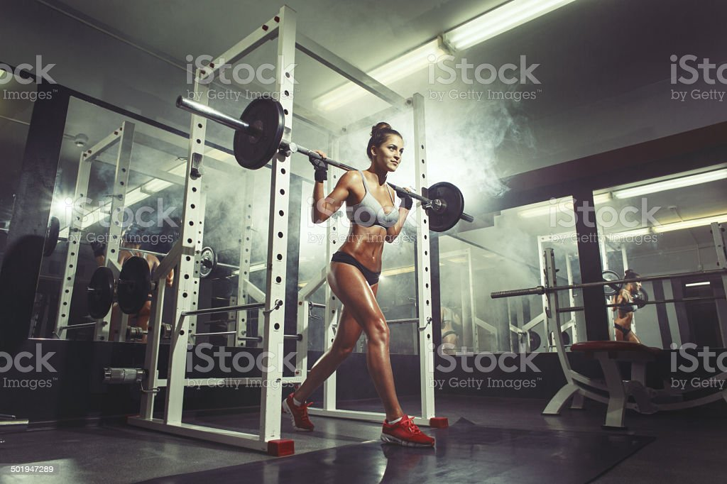 Young sexy girl in the gym doing squat stock photo