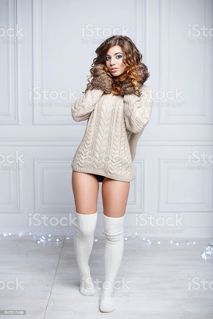 Young sexy girl in warm clothes and knitted mittens stock photo