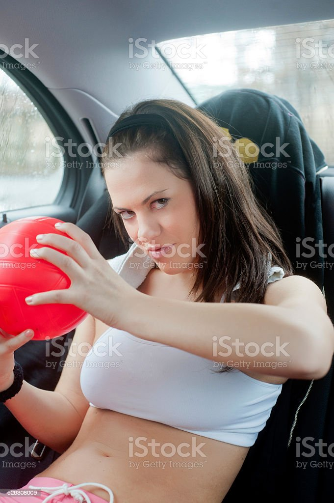Young sexy girl with a ball on a car backseat stock photo