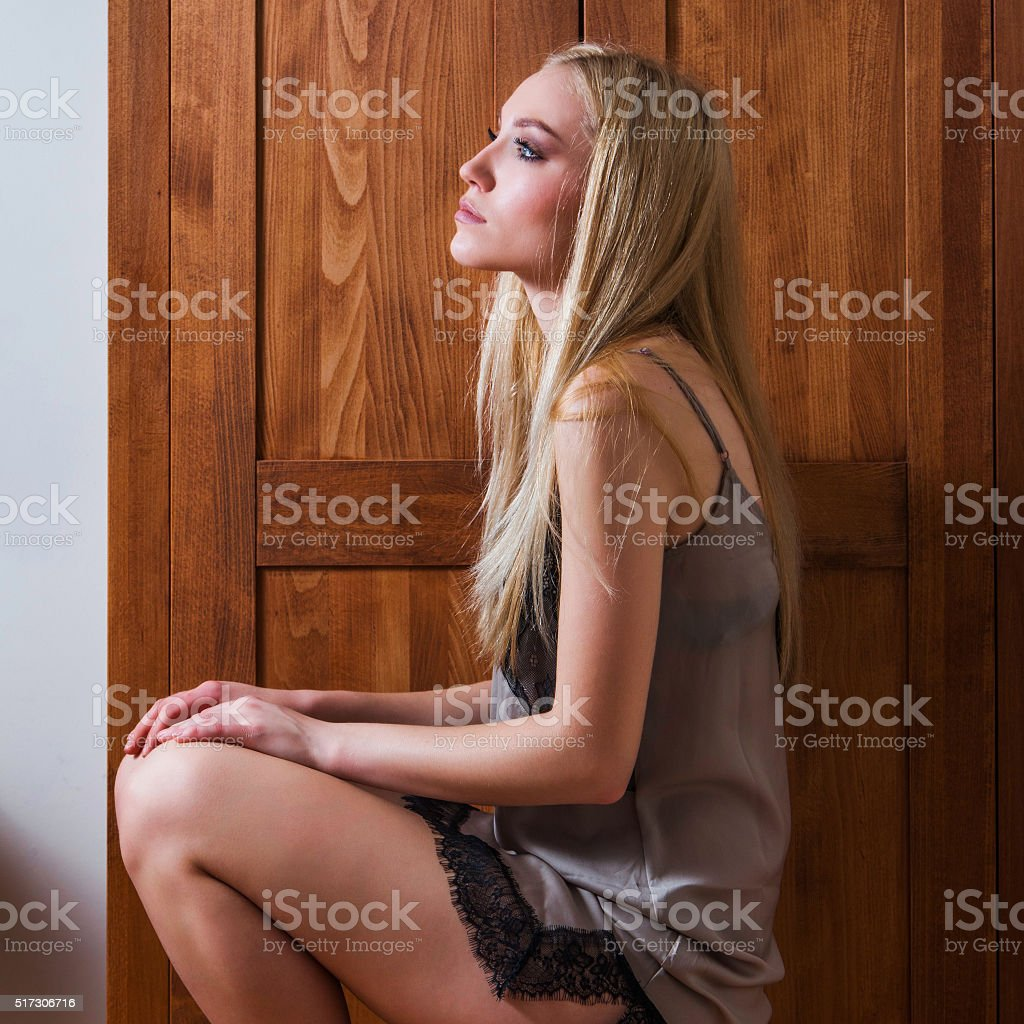 Young sexy lady in negligee in front of wooden locker stock photo