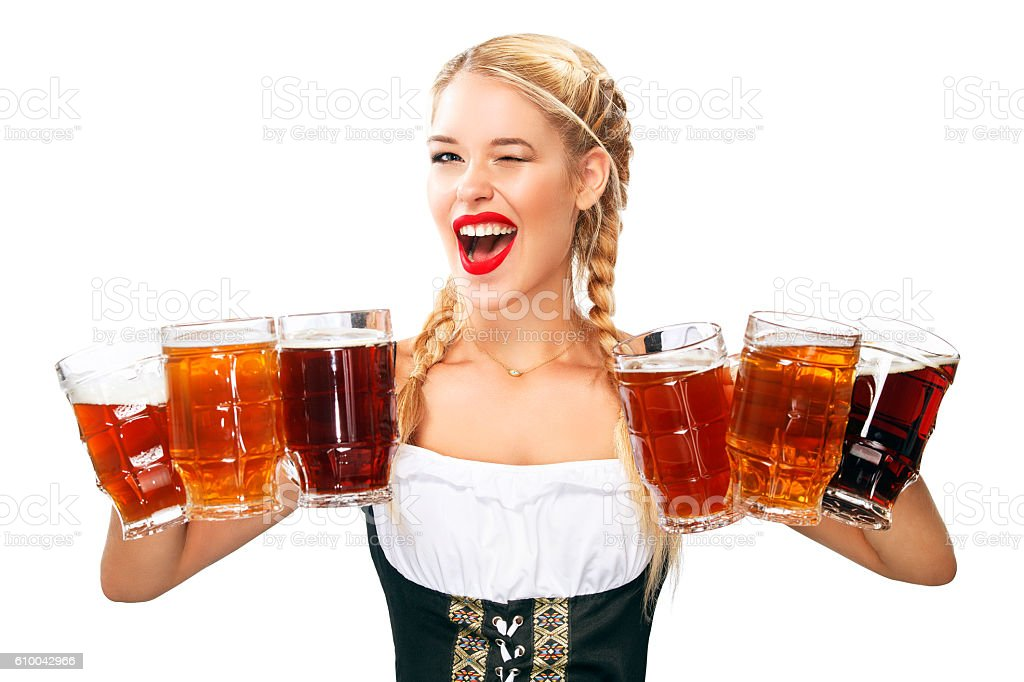 Young sexy Oktoberfest waitress, wearing a traditional Bavarian dress, serving stock photo
