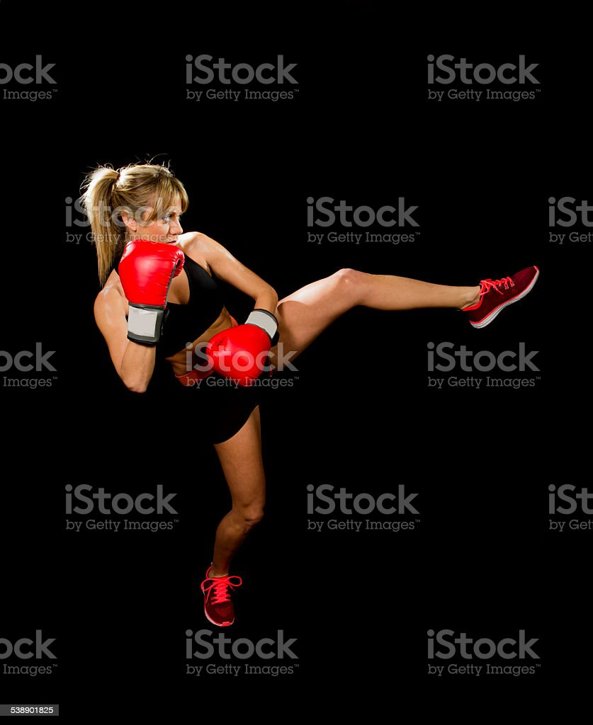 young sexy thai boxing girl fighting throwing kick attack stock photo