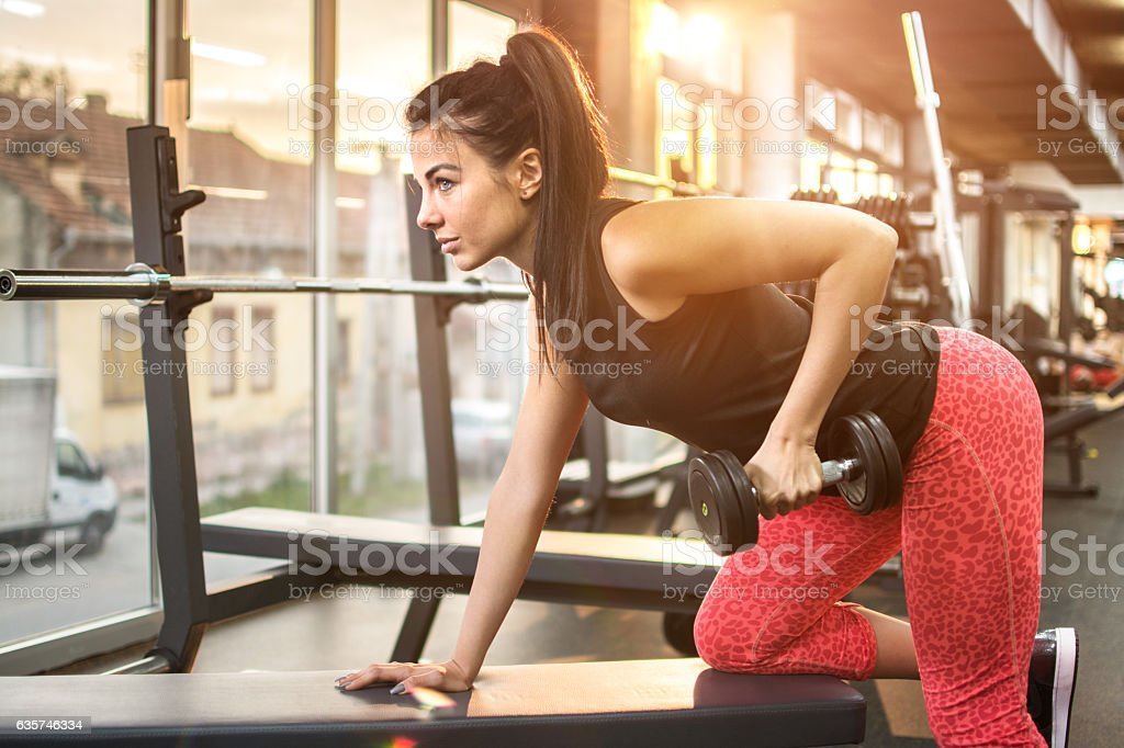 Young sexy woman doing exercises with dumbbell in gym. stock photo