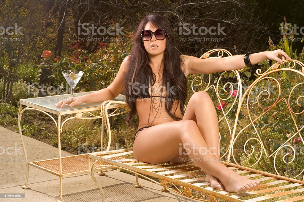 Young sexy woman in black swimsuit sunbathing on bench royalty-free stock photo
