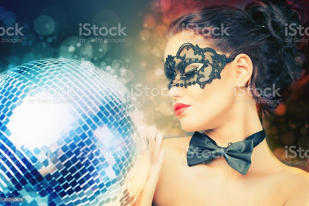 Young sexy woman in carnival mask keeping disco ball stock photo