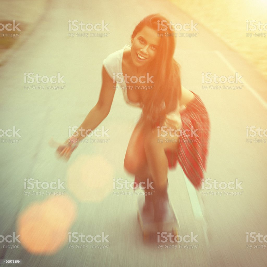Young sexy woman in jeans riding a skateboard with smile stock photo