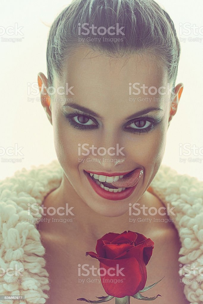 Young sexy woman smells red rose and licks her lips stock photo
