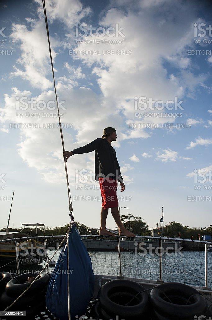 Young shipmate prepares to navigates boat departure from harbor stock photo